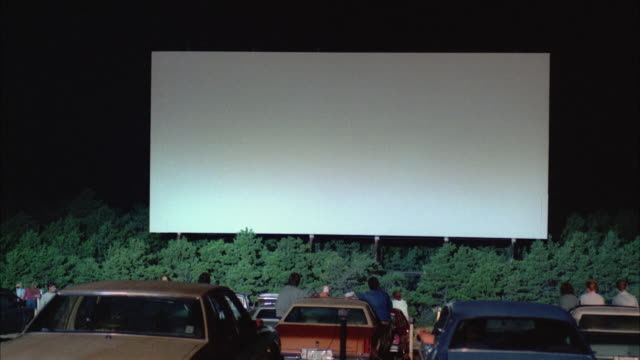 ms view of drive-in theater screen with cars in foreground - projection screen stock videos & royalty-free footage