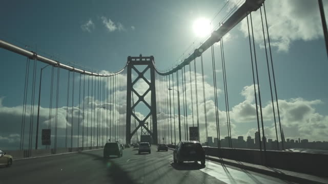 vídeos de stock, filmes e b-roll de ws slo mo pov view of driving over bay bridge with dowtown san francisco skyline / san francisco, california, united states - ponte