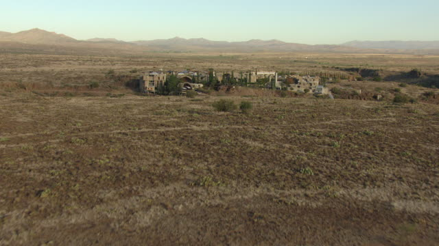ws aerial zi view of dry streambed to reveal buildings / arcosanti, arizona, united states  - apse stock videos & royalty-free footage