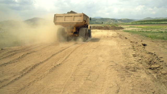 ws ts view of dump truck driving on construction site / malaga, andalusia, spain - dump truck stock videos and b-roll footage