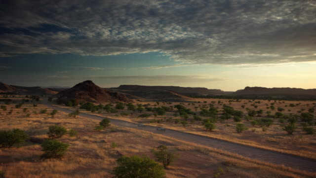 stockvideo's en b-roll-footage met ws t/l view of dusk falls on varied landscape of trees, grassland, hills, vast distances with vehicles leave dust trails as they speed through on lonely road / damaraland, windhoek, namibia - namibië