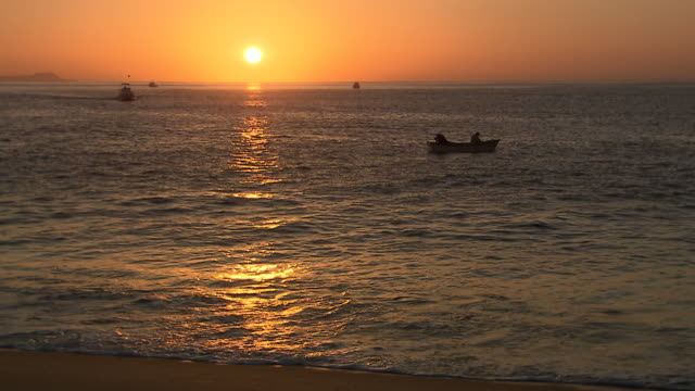 ws view of dusk sun low over horizon of two men in small fishing boat in midground, larger boat heads towards them, waves lap at shore of / cabo san lucas, baja california sur, mexico - fishing boat stock videos & royalty-free footage