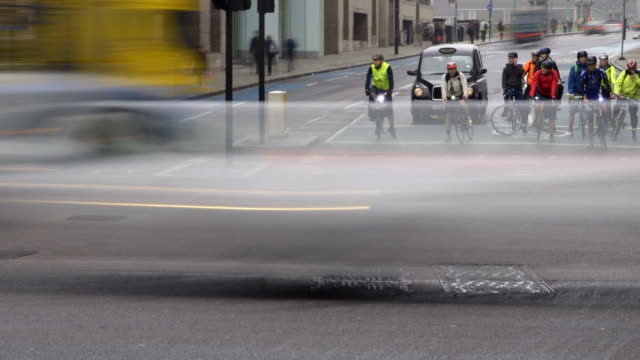 vídeos de stock, filmes e b-roll de ws t/l pan view of early morning rush hour traffic city of london with cars taxis buses and cyclist commuters stop start at traffic lights / london, greater london, united kingdom - stop placa em inglês