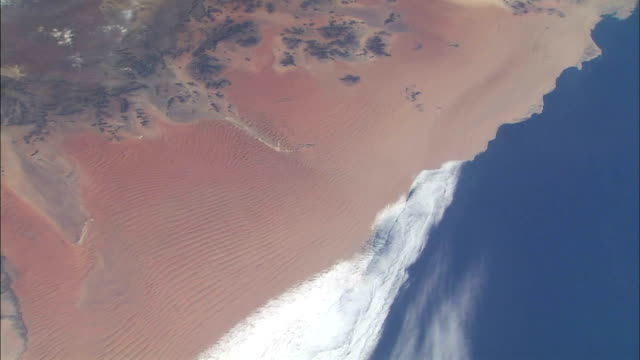 view of earth from space showing the coast of namibia in south western africa / coastline of the namib desert, red sand dunes, mountains and river... - sand dune stock videos & royalty-free footage