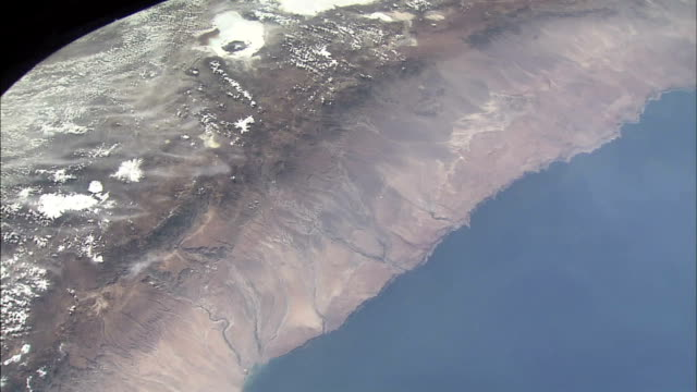 view of earth from space showing the coastline of northern chile with volcanoes in the andes mountains - mountain range stock videos & royalty-free footage