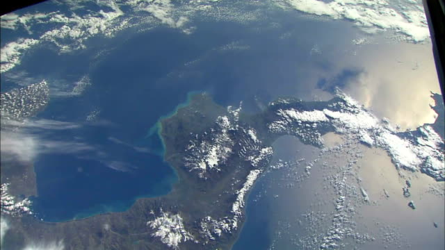 view of earth from space showing the island of sicily, the boot of italy, and clouds covering mt etna / coastline with sea and clouds. - territorio video stock e b–roll