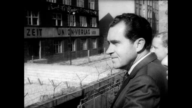 view of east berlin wall with fence around it / former vice president richard nixon arriving in car at checkpoint charlie / signs for checkpoint... - communism stock videos & royalty-free footage