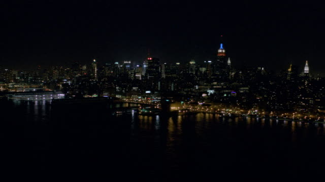 WS AERIAL View of East river looking toward mid town Manhattan with Empire State Building in city at night / New York, United States