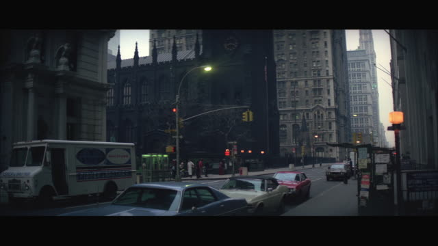 WS View of Eastern church, New York police car and white Porsche sports car by right to left past Trinity Church / New York City, USA