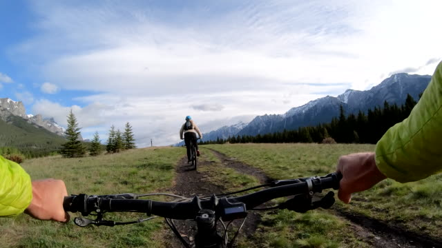 pov view of e-bike riding along mountain trail, behind other rider - サイクリングロード点の映像素材/bロール