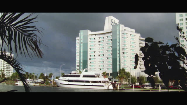 ws view of 'eden roc hotel' and sixty foot yacht docked in foreground / miami, florida, usa - anno 1994 video stock e b–roll