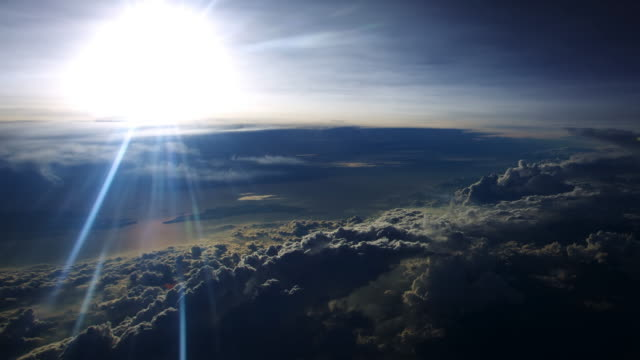 WS AERIAL T/L View of Edge of world and islands in sea seen below banks of clouds lit up by brilliant low sun / In Flight, Indonesia
