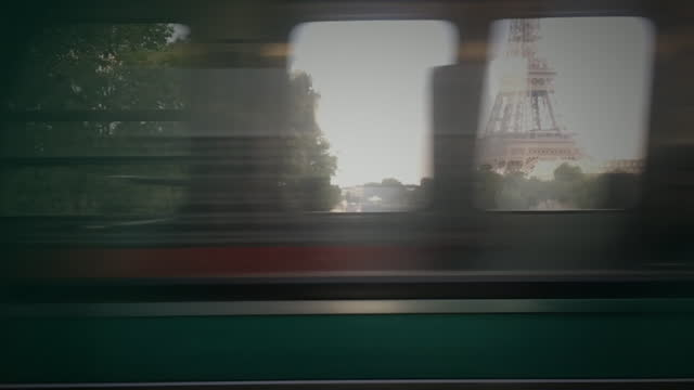 view of eiffel tower through passing metro train - passenger train stock-videos und b-roll-filmmaterial