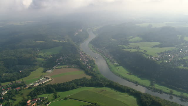 vídeos de stock, filmes e b-roll de ws aerial view of elbe river with towns, forest and cloudy sky / germany - rio elbe