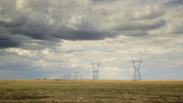 ws tu t/l view of electric pylon in field against sky / flagstaff, arizona, usa - flagstaff arizona video stock e b–roll