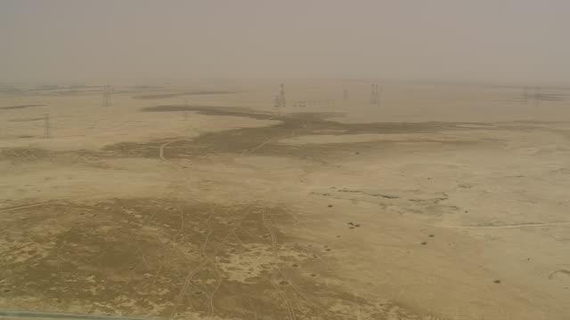 vidéos et rushes de ws aerial view of electricity poles at desert with city / qatar - qatar