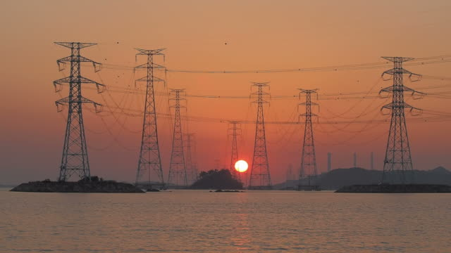 WS T/L View of Electricity Pylon and sun sinking below  horizon / Incheon, South Korea