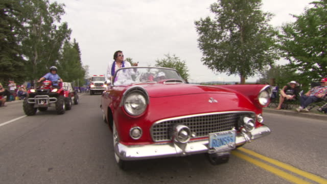 ws tu view of elvis presley impersonator riding on vintage red car during golden days festival kinross fort knox parade / fairbanks, alaska, united states - doppelgänger stock-videos und b-roll-filmmaterial