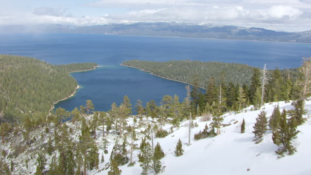 ws aerial pov view of emerald bay state park with rocky hilltop and lake tahoe in snow covered pine forest at northern sierra nevada / california, united states - state park stock videos & royalty-free footage