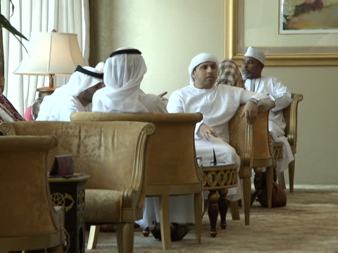 cu view of emirati and arab men traditionally dressed chatting in a hotel in abu dhabi - dish dash stock videos & royalty-free footage