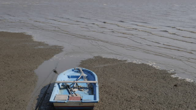 view of empty fishing boat on mud flat of maehyang-ri and high tide - tide stock videos & royalty-free footage