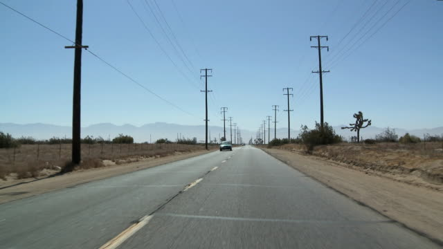 ws pov view of empty highway through desert / palmdale, california, usa    - telegraph pole stock videos and b-roll footage