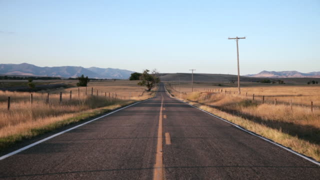 WS View of Empty hiway in prairie with mnountains in background at sunrise / Great Falls, Montana, United States