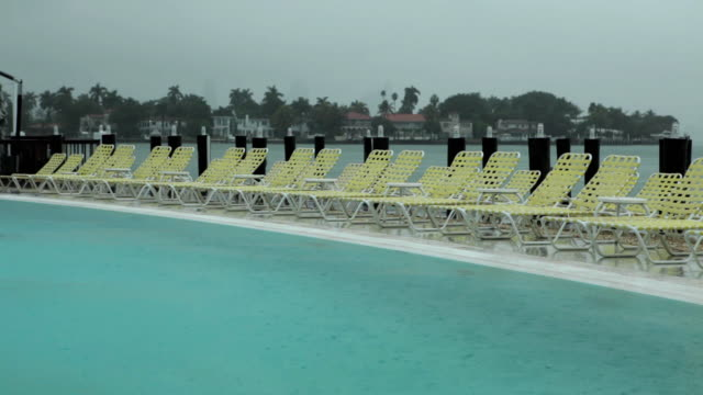 ws view of empty sun loungers next to rain-filled swimming pool / miami, florida, usa - sun lounger stock videos & royalty-free footage