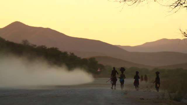 stockvideo's en b-roll-footage met ms view of end of day, himba family is walking back home from town / opuwo, kunene, namibia - namibië