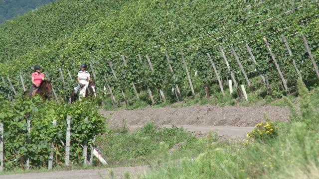 WS View of equestriennes riding at village Ayl, Saarburg country / Ayl, Saar-Valley, Rhineland-Palatinate, Germany