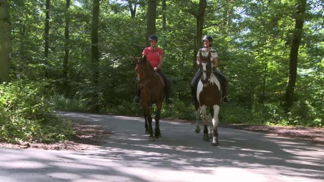 WS TS View of equestriennes riding at village Ayl, Saarburg country / Ayl, Saar-Valley, Rhineland-Palatinate, Germany