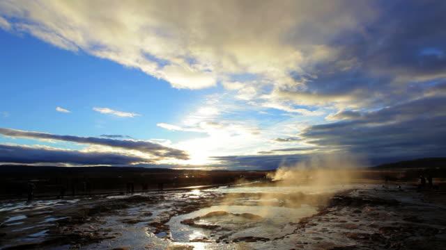 vídeos de stock, filmes e b-roll de ws view of erupting geyser strokkur at sunset / iceland - gêiser strokkur