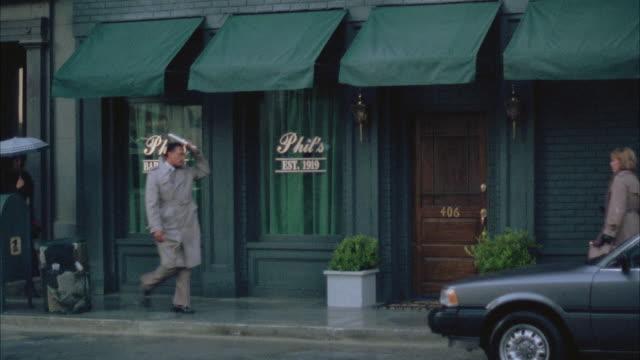 ms view of establish phil's bar raining - awning stock videos & royalty-free footage