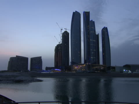 vidéos et rushes de view of etihad towers and their reflection in the gulf sea at dusk. - exclusivité