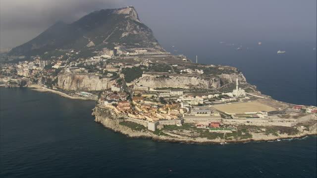 ws pan aerial view of europa point with cityscape / gibraltar city, gibraltar, spain  - gibraltar bildbanksvideor och videomaterial från bakom kulisserna
