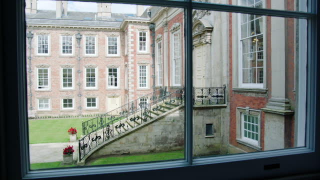 ms pan view of exterior door to kimbolton school through window / cambridgeshire, united kingdom - palacio stock videos & royalty-free footage