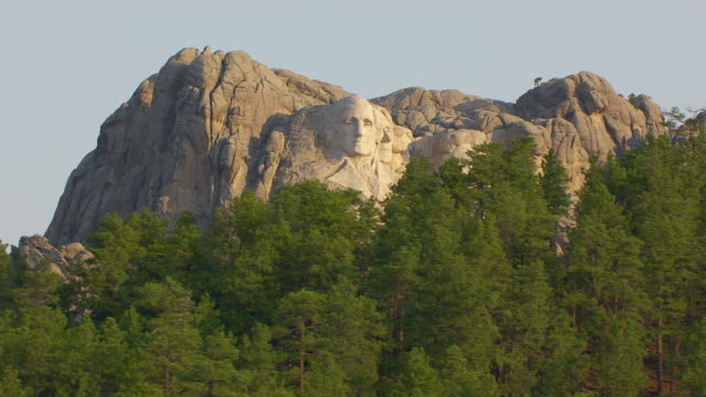 WS AERIAL TS View of faces from trees in foreground perspective of George Washington and Thomas Jefferson and Theodore Roosevelt and Abraham Lincoln at Mount Rushmore / South Dakota, United States