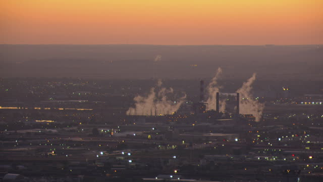 WS AERIAL View of factory towers with rising smoke into air and pink with yellow sunset / Denver, Colorado, United States