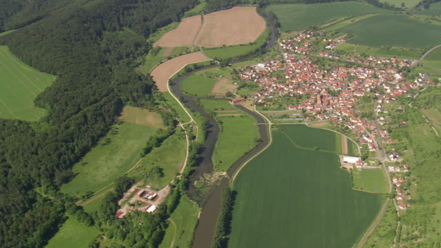 ws aerial view of falken and houses with werra river near national park heinich / germany - fluss stock-videos und b-roll-filmmaterial