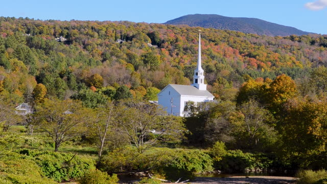 WS View of Fall colors in New England with Church steeple of Stowe Community Church in mountains foliage leaves / Stowe, Vermont, United States