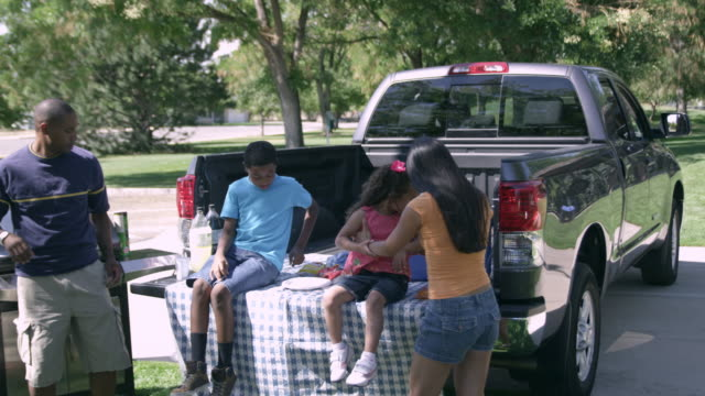view of family having tailgate picnic. - heckklappe teil eines fahrzeugs stock-videos und b-roll-filmmaterial