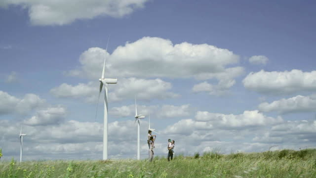 ms view of family walking towards  camera on a wind farm / toulouse, midi-pyrenees, france - fuel and power generation stock-videos und b-roll-filmmaterial