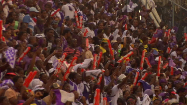 vídeos de stock, filmes e b-roll de ms pan zo zi view of fans waving flags in stands at football match / kingston, jamaica - cerca