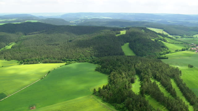 ws aerial view of farm field and hills with small town / germany - deutschland stock-videos und b-roll-filmmaterial