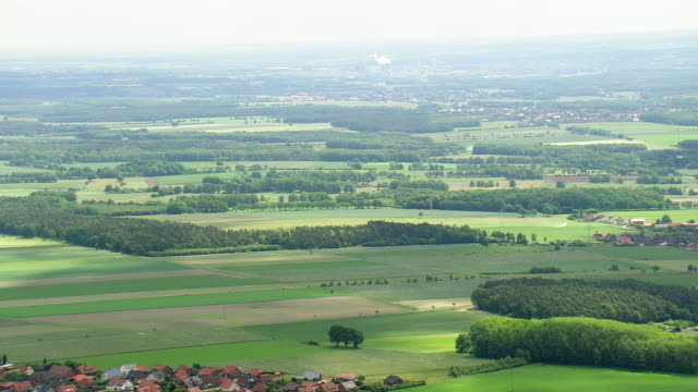 ws aerial view of farm field and houses with cooling tower of volkswagen factory in distance at wolfsburg / germany - wolfsburg lower saxony stock videos and b-roll footage