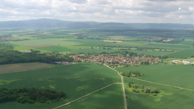 WS AERIAL View of farm field and houses with road way and hills in distance / Germany