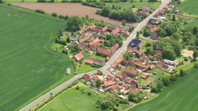 ws aerial zi view of farm field and houses with running vehicle on road way at ebeleben / germany - dorf stock-videos und b-roll-filmmaterial