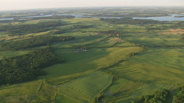 WS AERIAL View of farm field with Schaalsee lake at Zarrentin / Germany