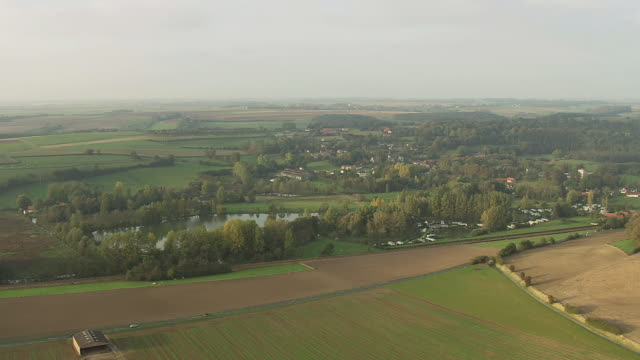 WS AERIAL PAN View of farm fields and town with busy roads / Pas de Calais, Italy