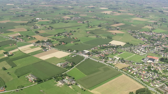 stockvideo's en b-roll-footage met ms aerial pan view of farm land at belgian landscape with houses / flanders, belgium - stadsdeel